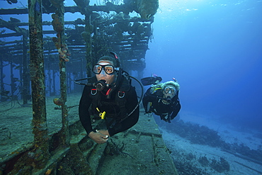 Two divers swimming along the remaining structure of a shipwreck.