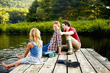Three people, two adults and a child relaxing on a jetty, with their feet in the water at the end of a day, Kingston, New York, USA