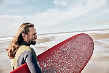 Man holding a full size surf board standing on beach looking out to sea, United Kingdom