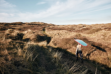 Man walking on a path in the sand dunes towards sea with surf board balancing on his head, United Kingdom