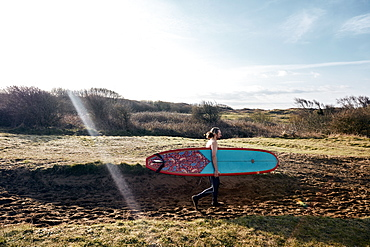 Man holding surf board walking along sandy path towards the sea, United Kingdom
