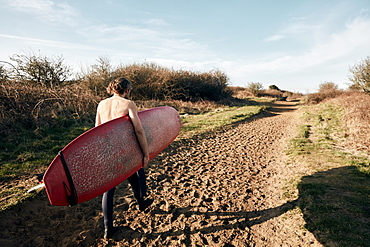 Man holding surf board walking along sandy path towards beach, United Kingdom