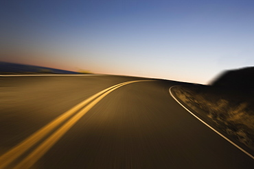 A blurred view of a road as a car drives on a highway just before sunrise, United States of America