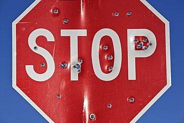 A stop sign that has been shot multiple times with a high powered rifle, United States of America
