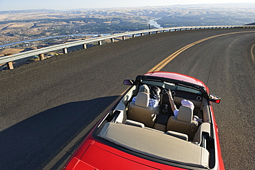Young Caucasian couple on a road trip in their convertible sports car near Lewiston, Idaho USA, United States of America