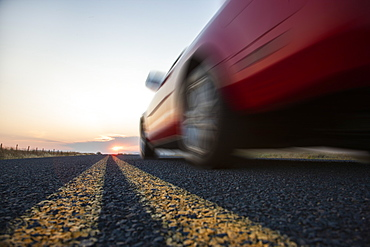 Low angle view looking up at the side of a convertible sports car on the road at sunset, United States of America