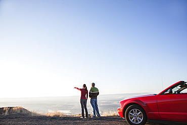 A young Caucasian couple admires the view at a rest stop in Eastern Washington, USA while on a road trip with their convertible sports car, United States of America