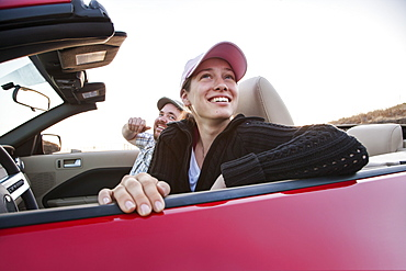 Caucasian couple parked in their sports car convertible, United States of America