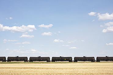 Oil train cars and fallow farmland, near Swift Current, Saskatchewan, Canada