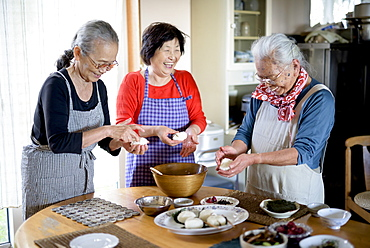 Three older women standing round a table in a kitchen, making sushi, Japan
