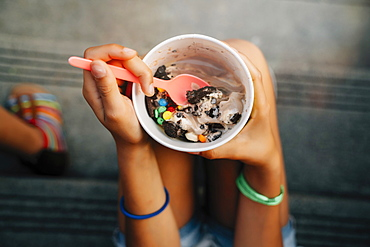High angle close up of girl sitting on steps eating ice cream, United States of America
