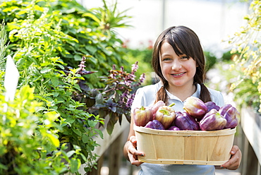 Summer on an organic farm. A girl holding a basket of fresh bell peppers.