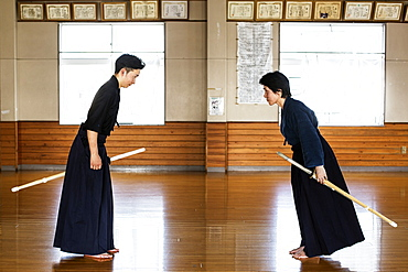 Female and male Japanese Kendo fighters standing opposite each other on wooden floor, bowing and greeting, Kyushu, Japan