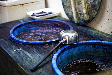 High angle close up of ladle and buckets with blue dye in a textile plant dye workshop, Kyushu, Japan