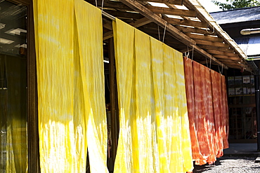 Freshly dyed bright yellow and orange fabric hanging outside a textile plant dye workshop, Kyushu, Japan
