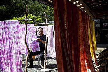 Japanese man sitting outside a textile plant dye workshop, hanging up freshly dyed pink fabric, Kyushu, Japan