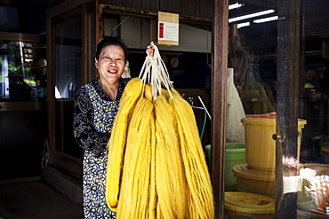 Japanese woman working in a plant dye workshop,  holding up freshly dyed bright yellow fabric, Kyushu, Japan