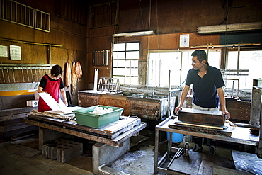 Two people, man and woman making traditional Washi paper. Trays of pulp and wooden frames and drying racks, Kyushu, Japan