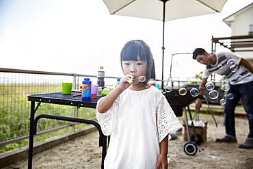 Portrait of Japanese girl wearing white shirt blowing soap bubbles, Kyushu, Japan