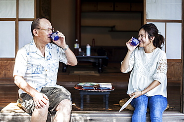 Japanese man and woman sitting on floor on porch of traditional Japanese house, drinking tea, Kyushu, Japan
