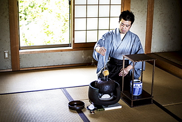 Traditional Japanese Tea Ceremony, man wearing kimono sitting on tatami mat using a Hishaku, a bamboo ladle, to pour hot water, Kyushu, Japan