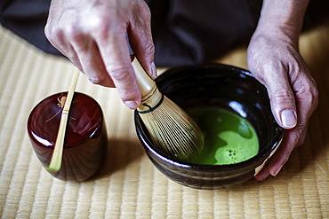 High angle close up of traditional Japanese Tea Ceremony, man using bamboo whisk to prepare Matcha tea, Kyushu, Japan