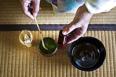 High angle close up of traditional Japanese Tea Ceremony, woman spooning green Matcha tea powder into bowl, Kyushu, Japan