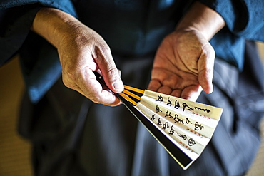 High angle close up of Japanese man wearing kimono holding Sensu fan, Kyushu, Japan