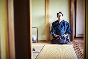 Japanese man wearing kimono kneeling on floor, on a tatami mat during tea ceremony, Kyushu, Japan