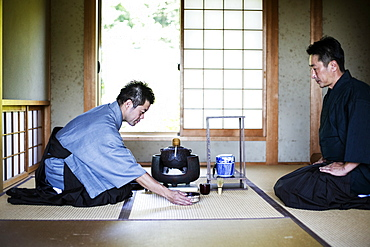 Two Japanese men wearing traditional kimonos kneeling on floor during tea ceremony, Kyushu, Japan