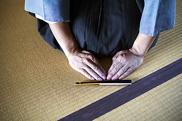 High angle close up of Japanese man kneeling on tatami mat in front of Sensu fan during a tea ceremony, used as a greeting, Kyushu, Japan