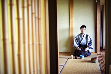 Japanese man wearing traditional kimono kneeling on tatami mat during tea ceremony, Kyushu, Japan