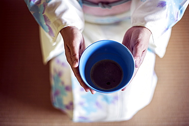 High angle close up of Japanese woman wearing traditional white kimono with blue floral pattern kneeling on floor during tea ceremony, holding blue tea bowl, Kyushu, Japan