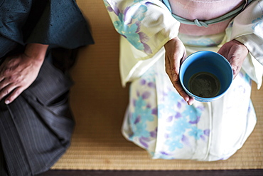 High angle close up of Japanese man and woman wearing traditional white kimono with blue floral pattern kneeling on floor during tea ceremony, holding blue tea bowl, Kyushu, Japan