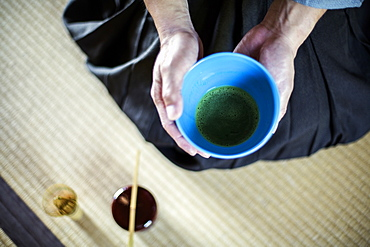 High angle close up of Japanese man wearing traditional kimono kneeling on floor holding blue bowl with Matcha tea during tea ceremony, Kyushu, Japan