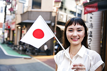 Smiling Japanese woman with long brown hair wearing white short-sleeved blouse standing in a street, holding small Japanese flag, Kyushu, Japan