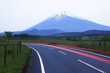 Blurred headlights on road before mountain, Japan, Japan
