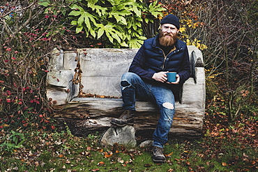 Bearded man wearing black beanie sitting on wooden bench in garden, holding blue mug, looking at camera, Berkshire, England