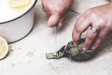 High angle close up of person cutting fresh artichoke with kitchen knife, Oxfordshire, England