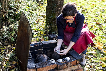 High angle close up of woman wearing red apron kneeling next to outdoor smoke fire pit, working on vase, England