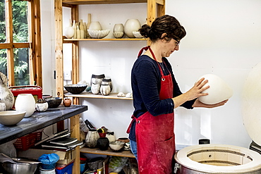 Woman wearing red apron standing in her workshop next to kiln, holding ceramic vase, England