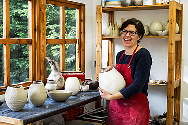 Woman wearing red apron standing in her workshop, holding ceramic vase, smiling at camera, England