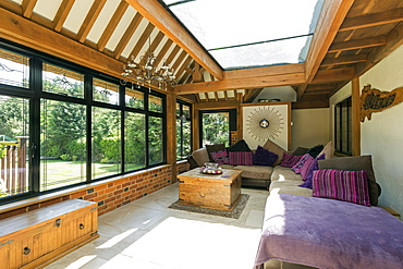 Cushioned benches in sunny conservatory, Farnham Royal, Buckinghamshire, UK