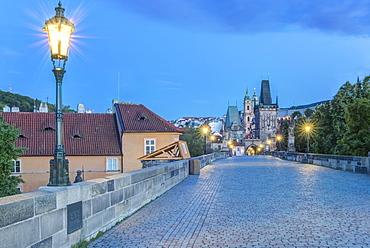 Illuminated streetlamps on cobblestone bridge at dawn, Prague, Czech Republic