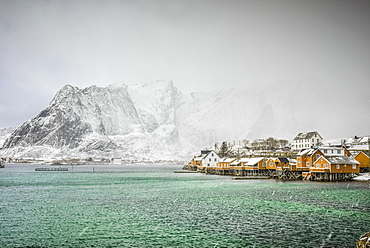 Snowy mountains overlooking rocky coastline, Reine, Lofoten Islands, Norway
