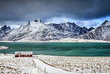 Snowy mountains overlooking ocean, Reine, Lofoten Islands, Norway