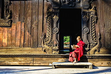 Asian monk reading by ornate doorway to temple