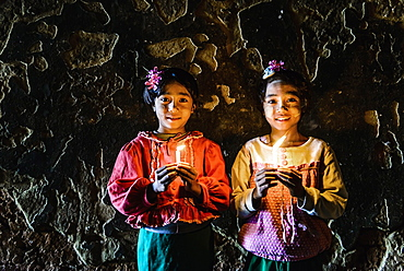 Asian girls holding candles in temple