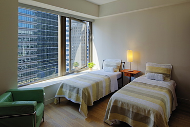 Twin beds in bedroom overlooking city skyscraper