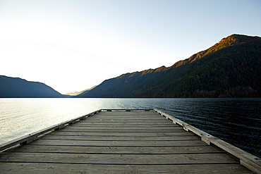 Wooden deck at lake under blue sky
